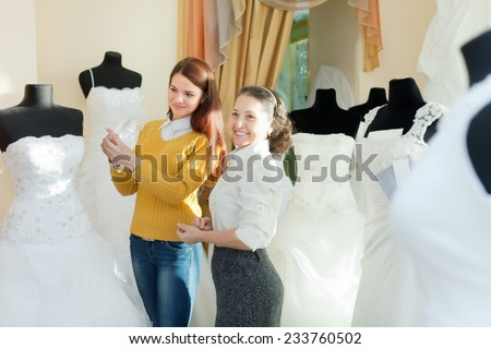 bride chooses bridal outfit at wedding store. Friendly shop consultant helps her - stock photo