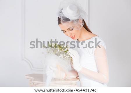 Bride. Closeup portrait smiling happy adult young woman retro style looking at holding smelling lilies Lilly of the valley flowers isolated white classic background. White dress gloves fascinator cap - stock photo