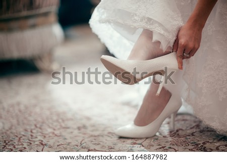 Bride dresses shoes before the wedding ceremony