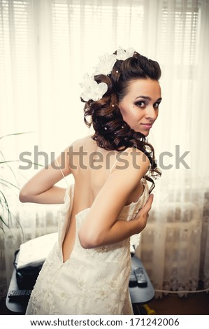 Bride dressing gown. bride preparing for a wedding. bride is getting dressed in the room. brunette young bride prepare for the event by makeup artist.