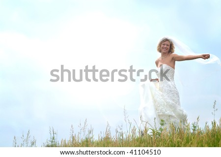 Bride embraces and dances with the sunbeams on a grassy hill. - stock photo