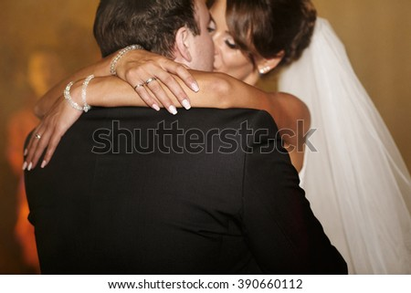 Bride embracing and kissing groom in the restaurant hall - stock photo