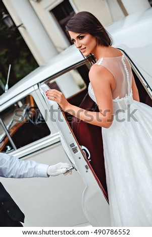 Bride entering classic car. Driver opening the door