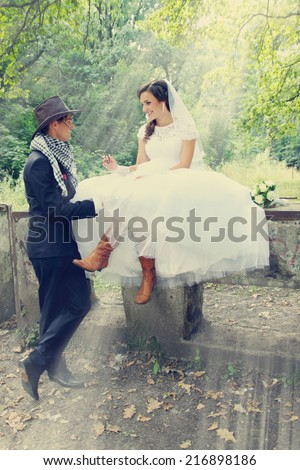 bride flirting with the groom in a cowboy hat - stock photo