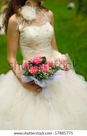 Bride from behind throw the bouquet from pink roses on old wall background - stock photo
