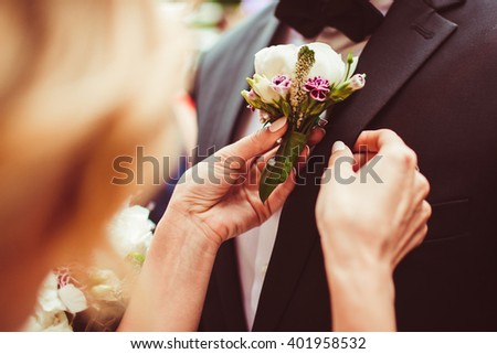 bride gives her groom a small beautiful bouquet - stock photo