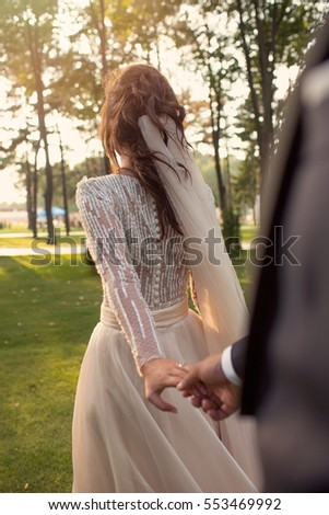 Bride & groom holding hands in nature