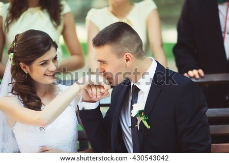 bride groom kisses hand, sitting on the bench
