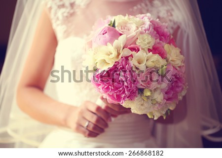 Bride holding a beautiful peonies bouquet - stock photo