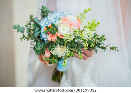 bride holding a beautiful wedding bouquet of white and blue, rosy  flowers, spring