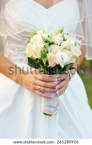Bride holding a beautiful white wedding bouquet. - stock photo