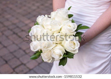 Bride Holding a Bouquet of White Roses - stock photo