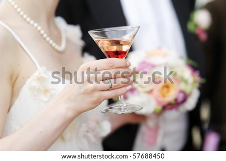 Bride holding a colorful cocktail in her hand - stock photo