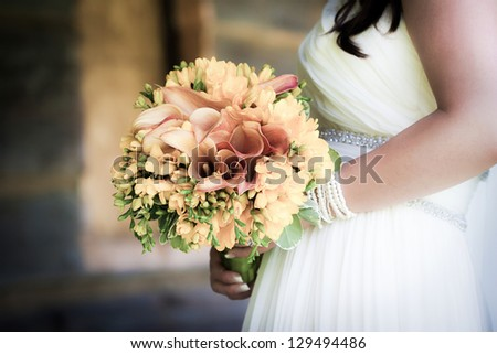 Bride holding a wedding bouquet - stock photo