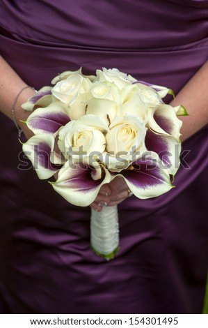 Bride Holding A Wedding Bouquet Of Purple Plus White Roses And Calla Lilies