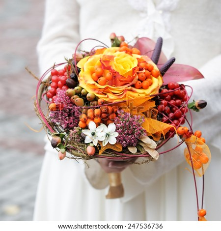 Bride holding beautiful orange wedding flowers bouquet  - stock photo