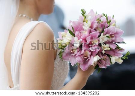 Bride holding beautiful pink wedding flowers bouquet - stock photo