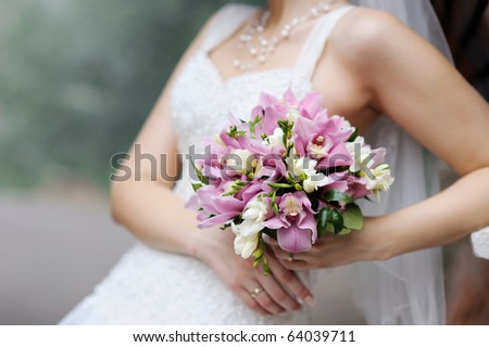 Bride holding beautiful pink wedding flowers bouquet - stock photo