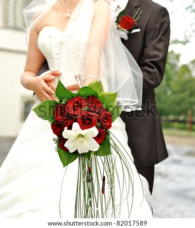 bride holding beautiful red roses. wedding flowers bouquet. selective focus - stock photo