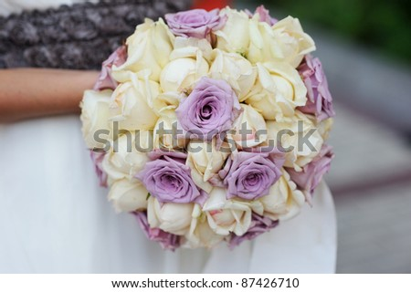 Bride holding beautiful wedding bouquet of pink and white roses - stock photo