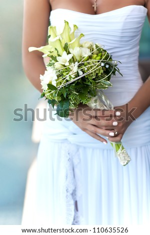 Bride holding beautiful wedding flowers bouquet - stock photo