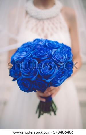 Bride holding blue wedding bouquet - stock photo