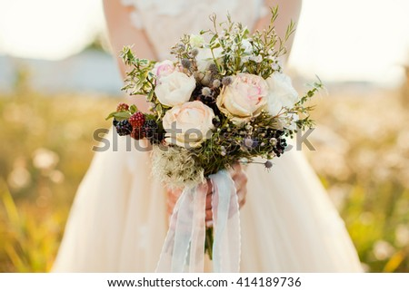 bride holding bouquet of roses, berries and eustoma