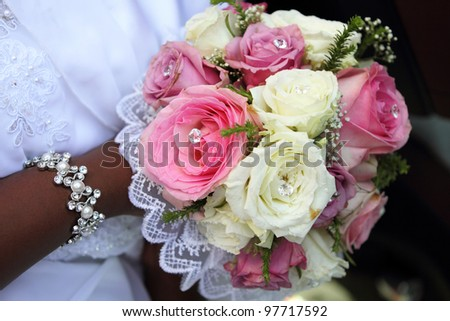 Bride holding bouquet with pink and white roses, African wedding. - stock photo