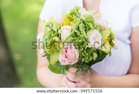 Bride holding bouquet with pink roses. Wedding