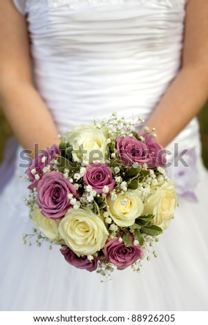 bride holding bouquet with yellow and purple  rosses
