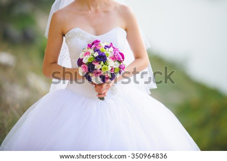 bride holding colorful wedding bouquet - stock photo