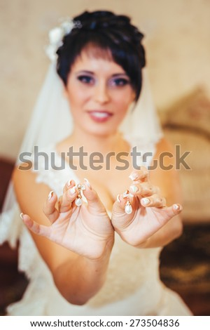 bride holding earrings. Portrait of a gorgeous woman adjusting her earring. Preparation moment for the wedding