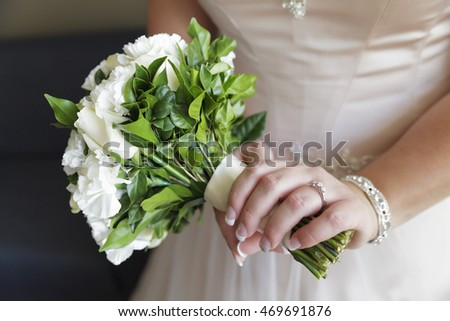 Bride holding flowers showing engagement ring