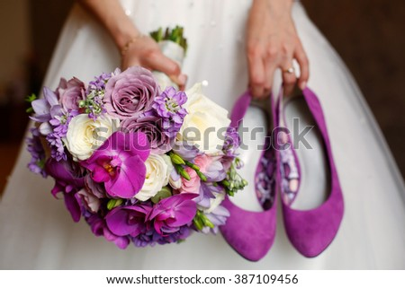 Bride holding shoes and colorful bouquet