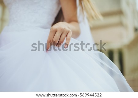 Bride holding the edge of a wedding dress