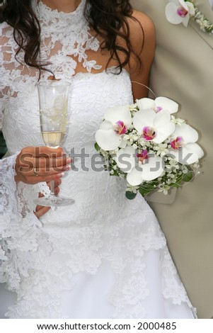 Bride holding the glass of champagne and bouquet - stock photo