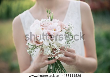 Bride holding wedding bouquet  - stock photo