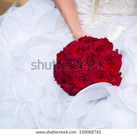 Bride holding wedding bouquet made of red roses - stock photo