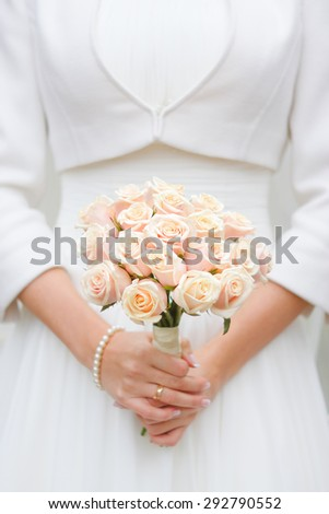 bride holding wedding bouquet of pink roses
