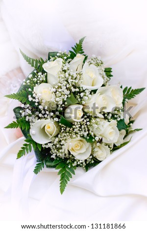 Bride holding wedding bouquet of white roses close up - stock photo