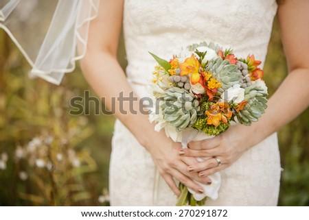 Bride holding wedding bouquet with Echeveria, Dahlia, Freesia, mini Hydrangea, Ranunculus, and Silver Brunia - stock photo