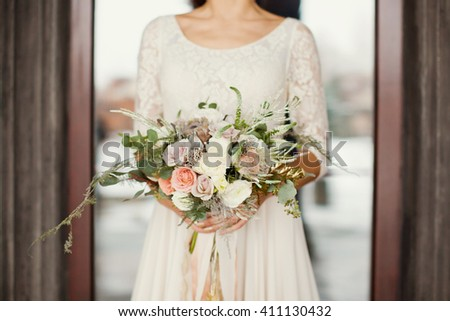 bride holding wedding bouquet with roses, protea and fern - stock photo