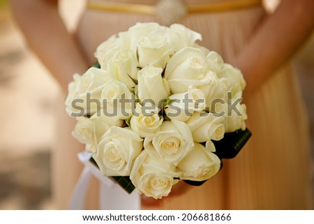 Bride holding wedding flower bouquet of yellow roses