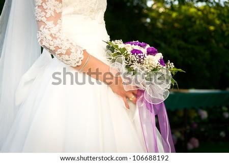 Bride holding wedding flowers. - stock photo