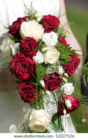 Bride holds bridal bouquet with roses in hand - stock photo