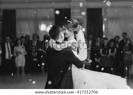 Bride hugs fiance while dancing in the restaurant - stock photo