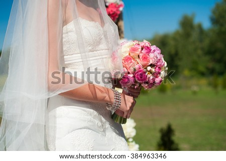 Bride in a dress with a veil, holding a beautiful bouquet. Outdoors. The average plan. lawn on the background - stock photo