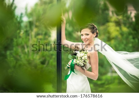Bride in a flowing dress with a blurred background lawn. - stock photo