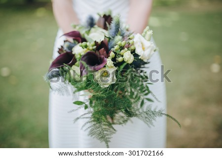 bride in a white dress holding a bouquet of purple flowers and greenery on the background of green grass - stock photo