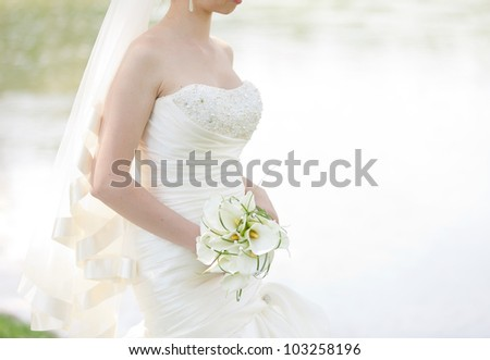 Bride in a white dress in summer green park near the lake - stock photo